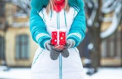 Glückliches hübsches Mädchen, das ein rotes Geschenk im Winterpark hält Lizenzfreie Stockbilder