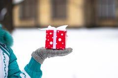 Glückliches hübsches Mädchen, das ein rotes Geschenk im Winterpark hält Lizenzfreies Stockbild