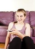 Glückliches hübsches Mädchen mit überwachendem Fernsteuerungsfernsehapparat Stockfotos