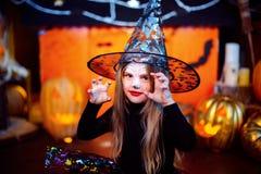 Glückliches Halloween Ein kleines schönes Mädchen in einem Hexenkostüm feiert mit Kürbisen lizenzfreie stockfotos