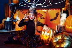 Glückliches Halloween Ein kleines schönes Mädchen in einem Hexenkostüm feiert mit Kürbisen lizenzfreie stockfotografie
