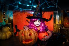 Glückliches Halloween Ein kleines schönes Mädchen in einem Hexenkostüm feiert mit Kürbisen lizenzfreie stockbilder