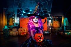 Glückliches Halloween Ein kleines schönes Mädchen in einem Hexenkostüm feiert mit Kürbisen lizenzfreies stockbild