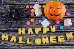 Glückliches Halloween fasst Dekoration mit furchtsamer Spinne, Süßigkeit und Kürbis auf hölzernem Hintergrund ab stockbild