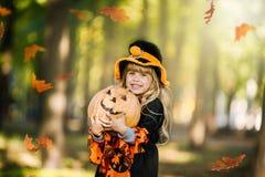 Glückliches Halloween Nette kleine Hexe mit einem Kürbis in den Händen lizenzfreie stockbilder