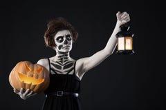 Glückliches Halloween Porträt der schwarzen Hexe mit furchtsamem Make-up über schwarzem Hintergrund Halten des Kürbises und der L stockbild