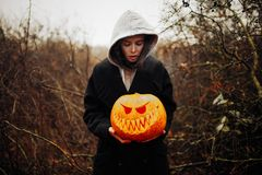 Glückliches Halloween-Porträt der schwarzen modernen Lebensstilhexe in der Haube und schwarzer Mantel überziehen stockfotografie