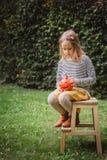 Glückliches Halloween Schöne lächelnde Kleinkindsitze auf Holzstuhl und Griffen wenig Kürbis Jack OLanterns draußen stockbild