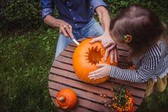 Glückliches Halloween Vater und Tochter, die Kürbis für Halloween außerhalb der hohen Winkelsicht, Hände schnitzen Glückliche Fam stockfotos