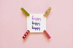 ` Glückliches ` handgeschrieben mit Aquarell in der Kalligraphieart, Miniaturwäscheklammern Flache Lage Stockfoto
