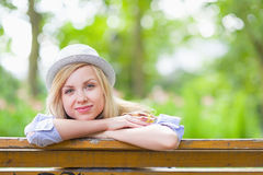 Glückliches Hippie-Mädchen, das im Park sitzt Stockbild