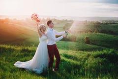 Glückliches Hochzeitspaar mit buttle von champaine und spritzt vom Champagner lizenzfreie stockbilder