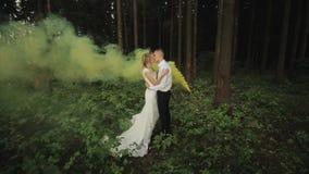 Glückliches Hochzeitspaar umarmt und küsst sich im Holz mit gelbem Rauche im Hintergrund stock video