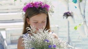 Glückliches intelligentes Mädchen, das mit Blumen und dem Lächeln bewundert langsam stock footage