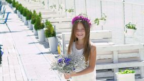 Glückliches intelligentes Mädchen, das mit Blumen und dem Lächeln bewundert langsam stock video