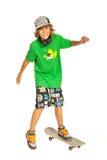 Glückliches jugendlich auf Skateboard in der Aktion Lizenzfreie Stockfotos