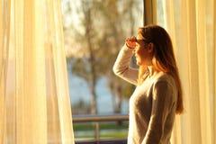 Glückliches jugendlich durch ein Fenster zu Hause kundschaften lizenzfreies stockfoto