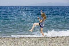 Glückliches jugendlich genießt die Ferien, die das Wasser am Strand von Sizilien treten Lizenzfreies Stockfoto