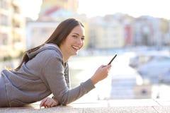 Glückliches jugendlich haltenes Telefon, das Kamera betrachtet stockfotos