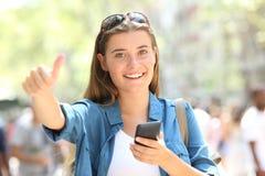 Gl?ckliches jugendlich haltenes Telefon, das oben Daumen gestikuliert lizenzfreie stockfotos