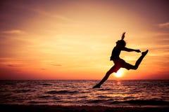 Glückliches jugendlich Mädchen, das auf den Strand springt Lizenzfreie Stockbilder