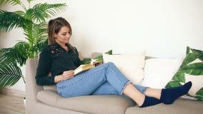 Glückliches jugendlich Mädchen, das auf Sofa am Wohnzimmer beim ihr neues Lieblingsbuch zu Hause lesen stillsteht stock footage