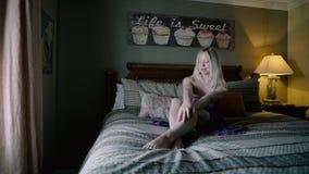 Glückliches jugendlich Mädchen, das an den Hotel ` s Wohnungen auf dem Bett sich entspannt Mädchen schließt am Fenster zu Sommerf stock video footage