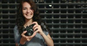 Glückliches Jugendlich-Mädchen, das Foto durch Weinlese-Film-Kamera in Front Of Metal Grid Fence macht stock footage