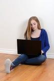 Glückliches jugendlich Mädchen, das Laptop verwendet Lizenzfreie Stockbilder