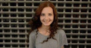 Glückliches jugendlich Mädchen, das vor Metallzaun des Sperrgebiets lächelt stock footage