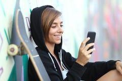 Glückliches jugendlich Mädchen des jungen Schlittschuhläufers, das ein intelligentes Telefon verwendet Lizenzfreie Stockfotografie