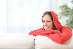 Glückliches jugendlich Mädchen im Rot, das zu Hause aufwirft Stockfotografie
