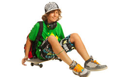 Glückliches jugendlich Sitzen auf Skateboard lizenzfreie stockfotos
