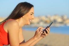 Glückliches jugendlich Suchen am intelligenten Telefon auf dem Strand stockbild
