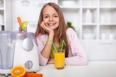 Glückliches Jugendlichmädchen, das in der Küche mit einem frischen zusammengedrückt sitzt lizenzfreies stockfoto