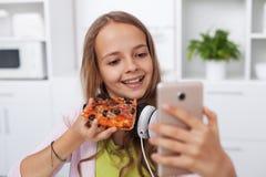 Glückliches Jugendlichmädchen, das ein selfie in der Küche aufwirft mit einer Scheibe der Pizza nimmt lizenzfreie stockfotografie