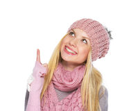 Glückliches Jugendlichmädchen im Winterhut zeigend oben auf Kopienraum Stockbild