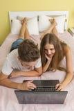 Glückliches Jugendlichmädchen und -junge, die einen Laptop aufpasst stockfotos