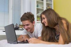 Glückliches Jugendlichmädchen und -junge, die einen Laptop aufpasst lizenzfreie stockbilder