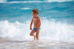 Glückliches Jungenkind, das Spaß im Meerwasser hat Stockfoto
