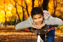 Glückliches Jungenlächeln, das auf Fahrradheck legt Lizenzfreie Stockfotografie