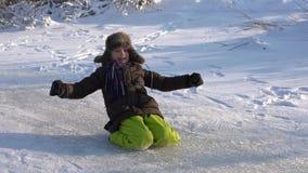 Glückliches Jungenreiten auf seinen Knien auf dem See, der eingefroren wurde Gefrorener und sonniger Wintertag Langsame Bewegung stock footage
