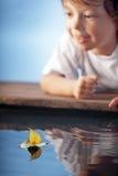 Glückliches Jungenspiel im Blattschiff stockfotos
