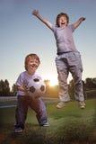 Glückliches Jungenspiel im Fußball Stockbild