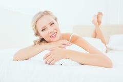 Glückliches junges blondes Lügen auf ihrem Bett, das an der Kamera lächelt Stockbild