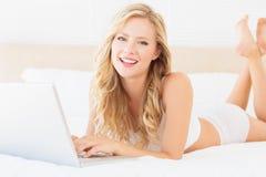 Glückliches junges blondes Lügen auf ihrem Bett unter Verwendung des Laptops Lizenzfreie Stockfotos