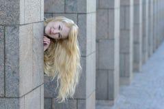 Glückliches junges blondes Mädchen, das heraus zwischen von den Spalten schaut Lizenzfreie Stockfotografie