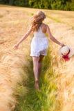 Glückliches junges blondes Mädchen im weißen Kleid mit laufendem Th des Strohhutes Stockbilder