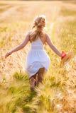 Glückliches junges blondes Mädchen im weißen Kleid mit laufendem Th des Strohhutes Stockbild