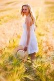 Glückliches junges blondes Mädchen im weißen Kleid mit laufendem Th des Strohhutes Stockfotos